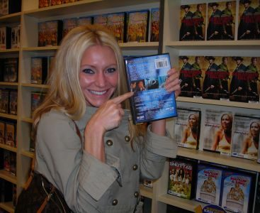 Carey in Silent Scream - Carey Torrice in a video store holding a DVD with her on the back from a movie she starred in called Silent Scream