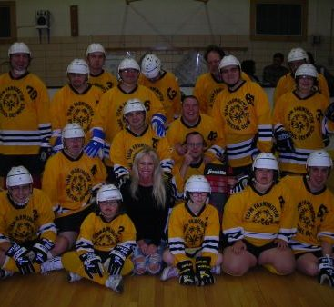 Carey with Team Farmington - Carey poses with Team Farmington Special Olympics hockey team at a game in Farmington