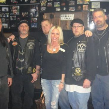 """Detroit Vigilante's M/C Charity Fundraiser - Carey poses with her friends from the Detroit Vigilante's Motorcycle Club members at their clubhouse. The Vigilante's M/C hosted a fundraiser to help a five year old child who was mauled by a pit bull. Carey Torrice supported the Vigilante's during this charitable event.  Vigilante's President """"Bam Bam"""" organized this event."""